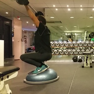 Squat with overhead bar on bosuball