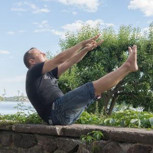 Boatpose in July 4th 2018. I bring a  Navasana or  Boatpose near  Södertuna Castle. This pose can be entered in a three-fold way: bend legs with holding knees for balance -> let go of knee