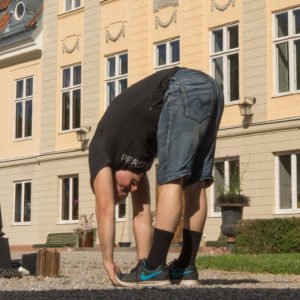 Standing forward fold in July 3rd 2018. I bring an  Uttanasana or  Standingforwardfold in front of  SödertunaSlott, outside  Gnesta,  Sweden.