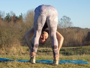 Uttanasana or standing forward fold in sunshine