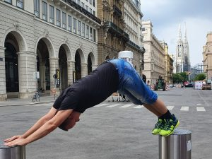 Downward Facing Dog in July 15th 2019. Doing a Adho Mukha Svanasana Downward Facing Dog with the iconic Votivkirche, Vienna in the background. Inversions means heart over head, and downdog is