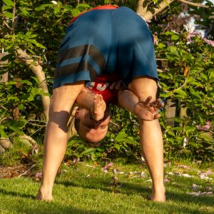 Tortoise pose in June 6th 2021. The Tortoisepose is very tough for me. I had it in another challenge today, so I bring a standing variation. Blooming magnoliatrees in the background.